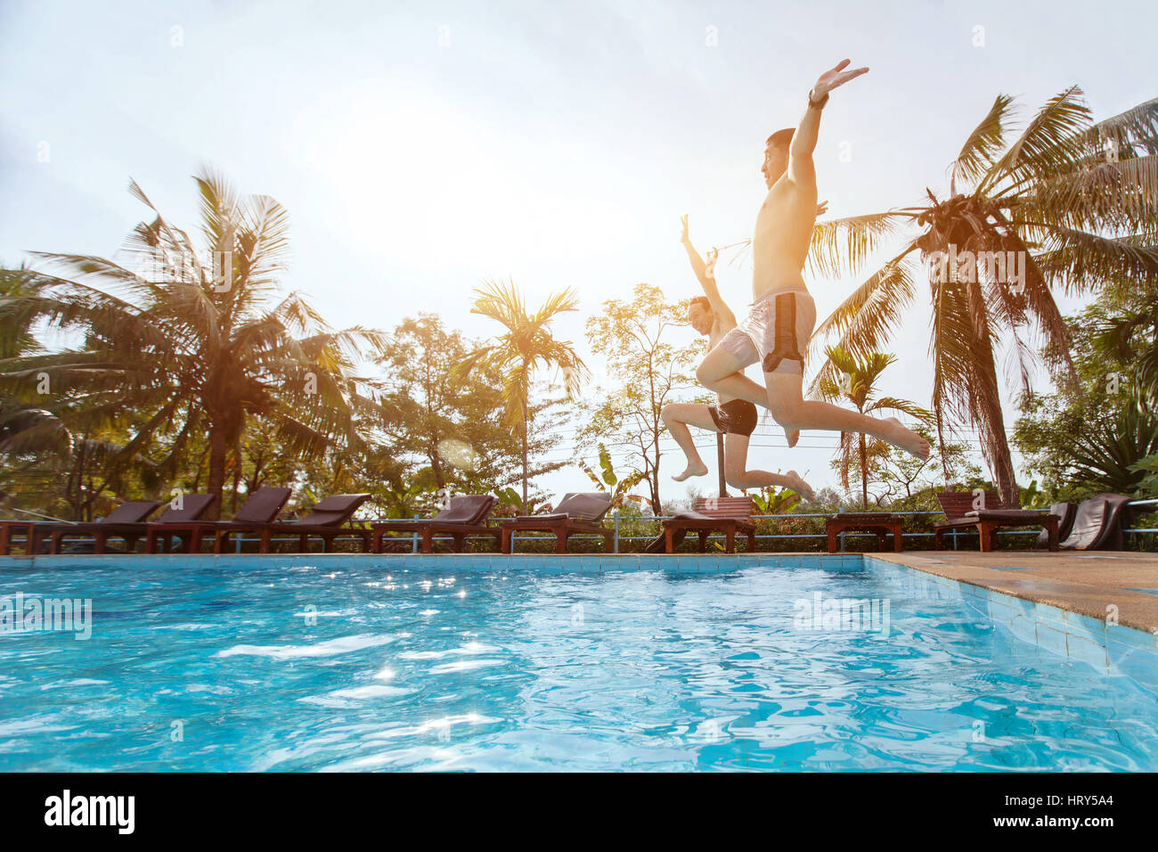 people jumping to the swimming pool, beach holidays, friends having fun together - Stock Image