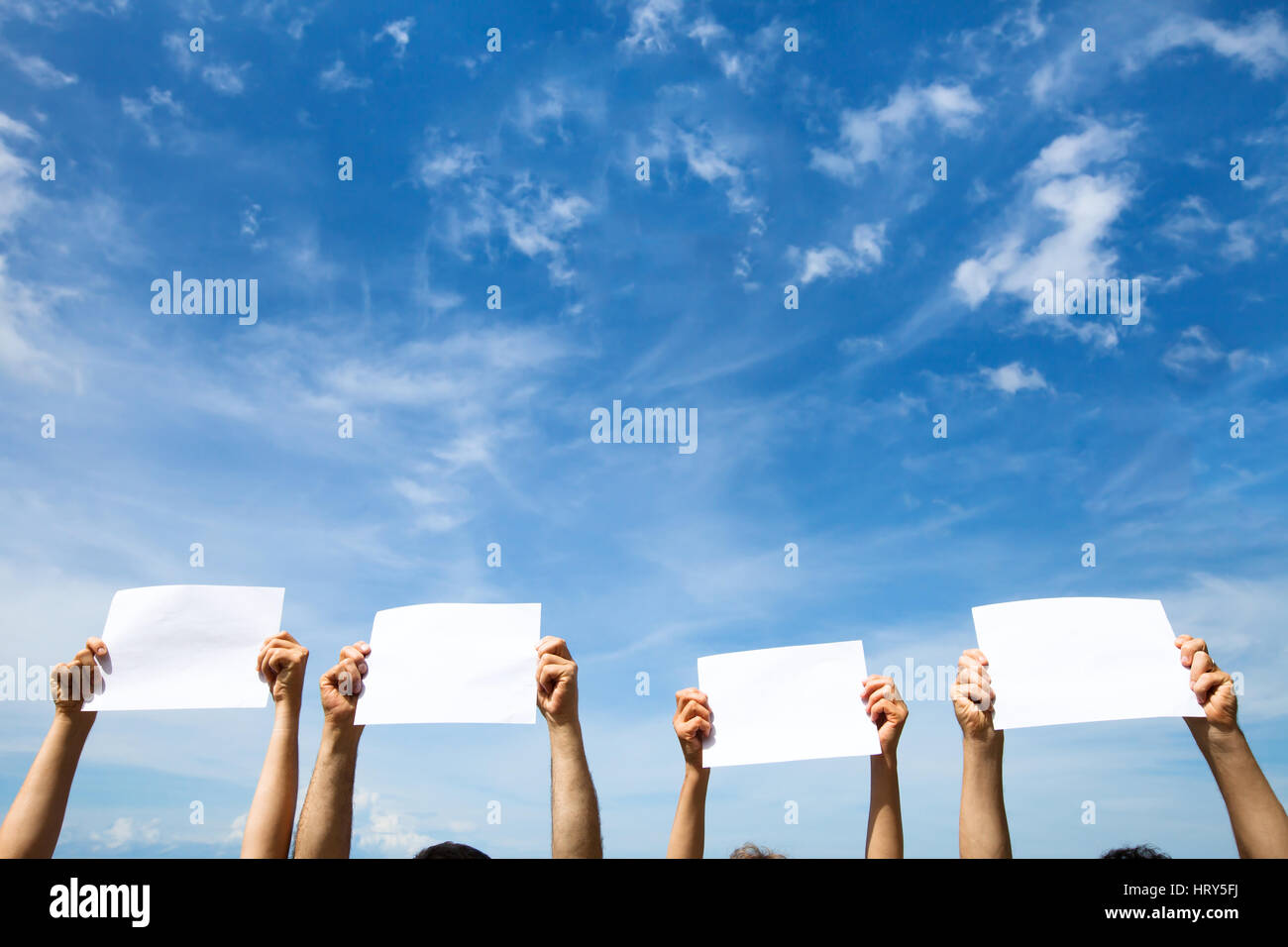 group of people holding empty blank paper signs on blue sky background - Stock Image