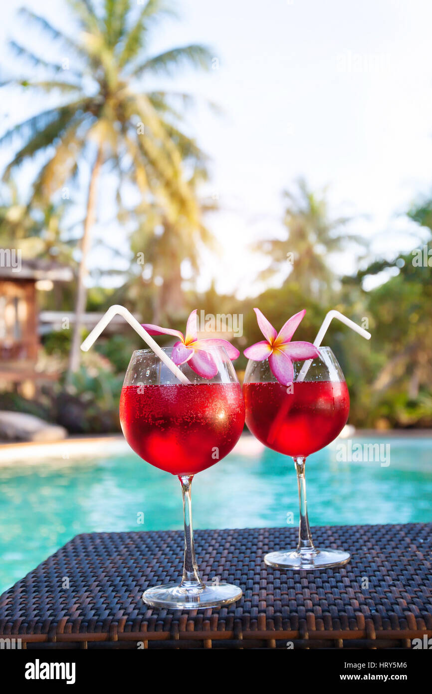 luxurious beach hotel, two beautiful exotic cocktails near swimming pool, holidays or relaxation concept - Stock Image