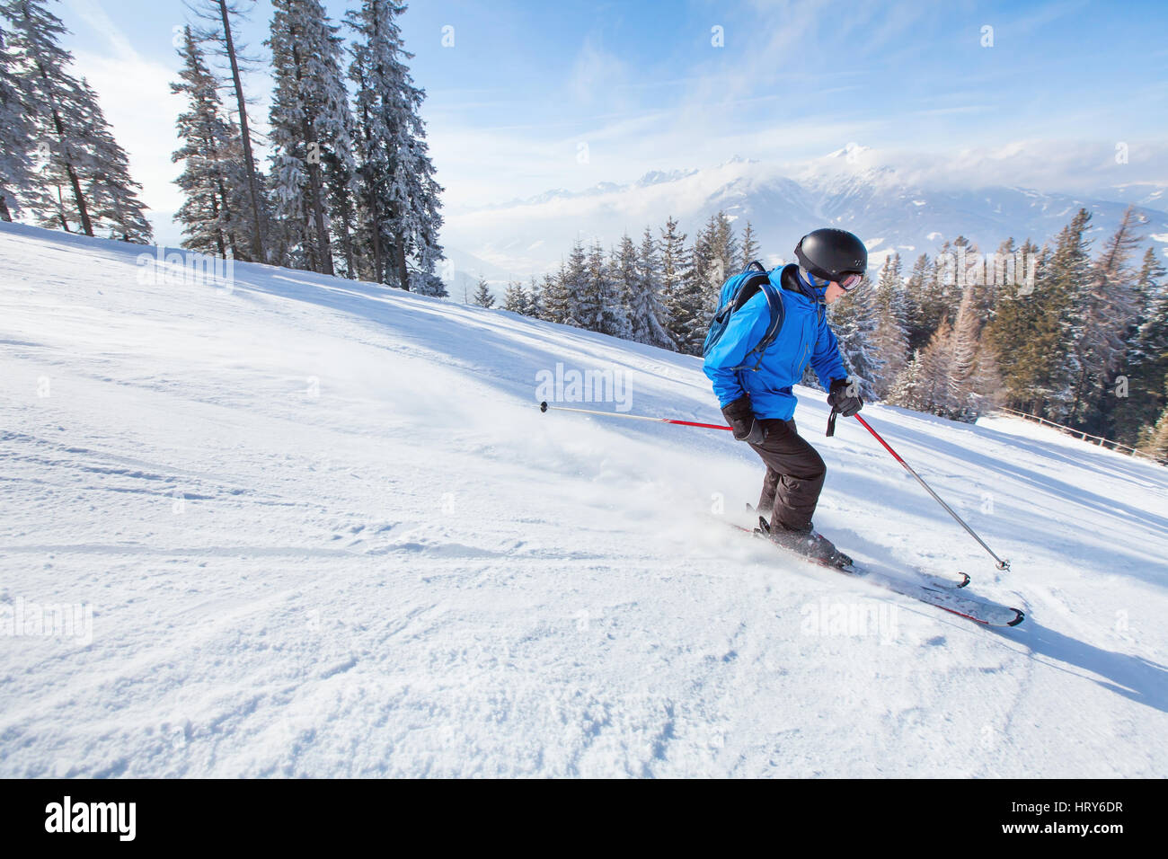 downhill skiing, skier going fast down the mountain, winter sport background - Stock Image