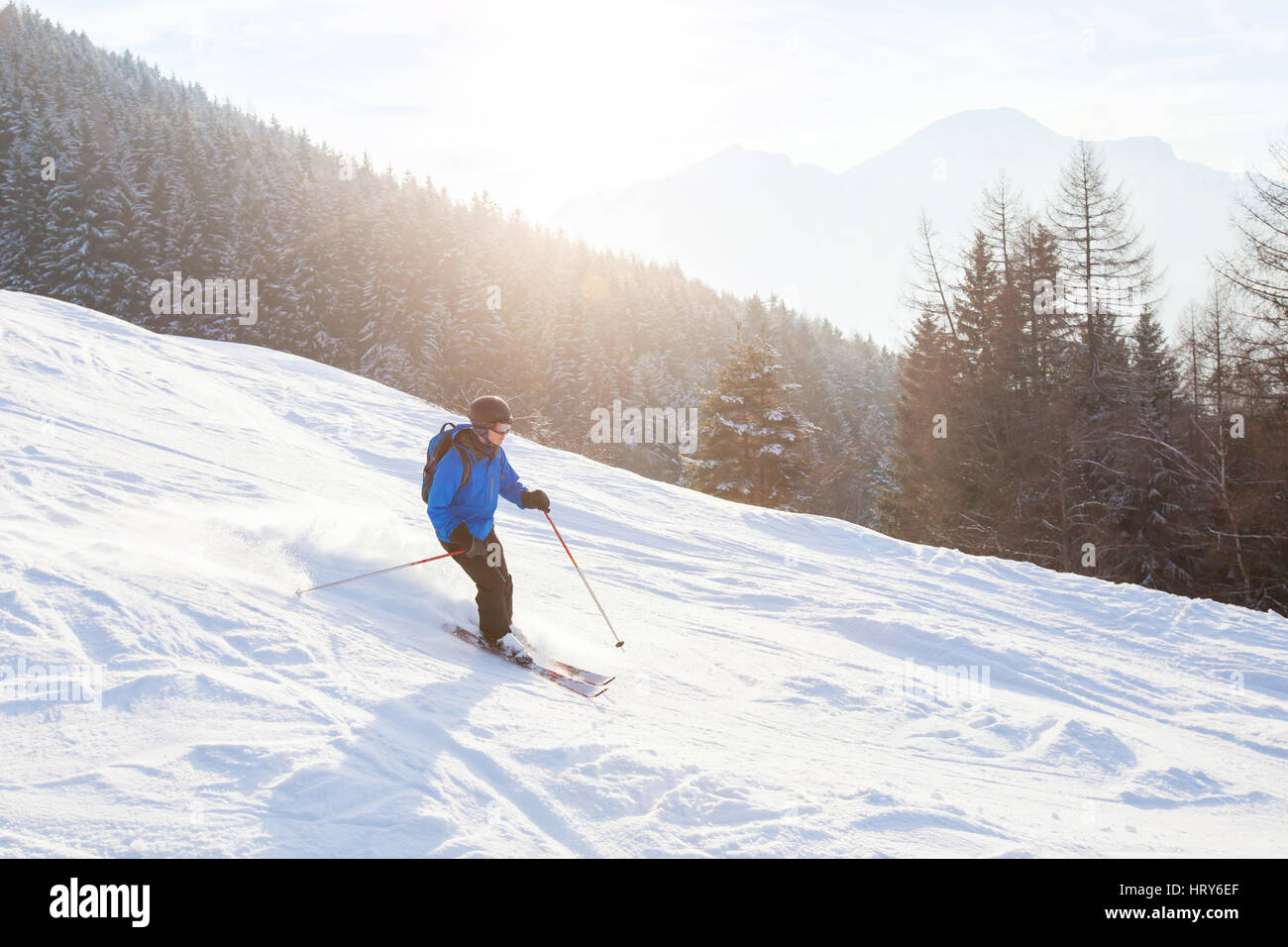skier in sunset mountains, downhill skiing - Stock Image