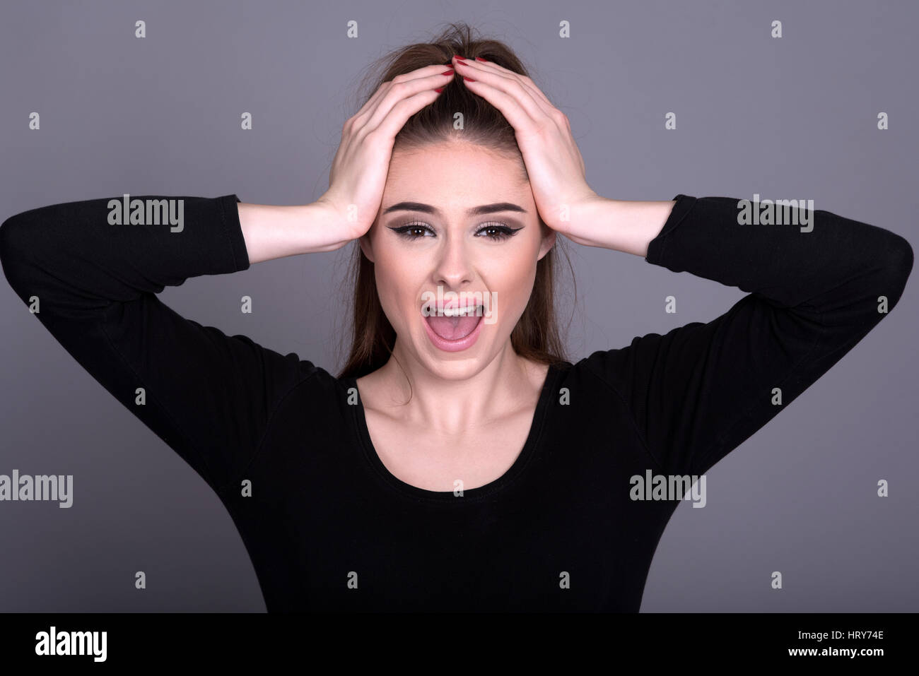 Young woman with hands on head shouting - Stock Image
