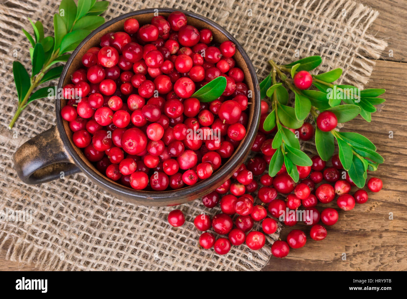 Cranberries over burlap background. Top view - Stock Image