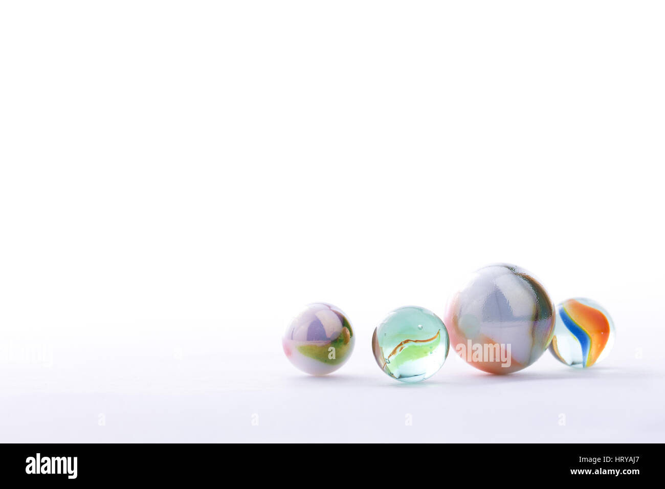 Close up photo of marbles, isolated in front of a white background - Stock Image