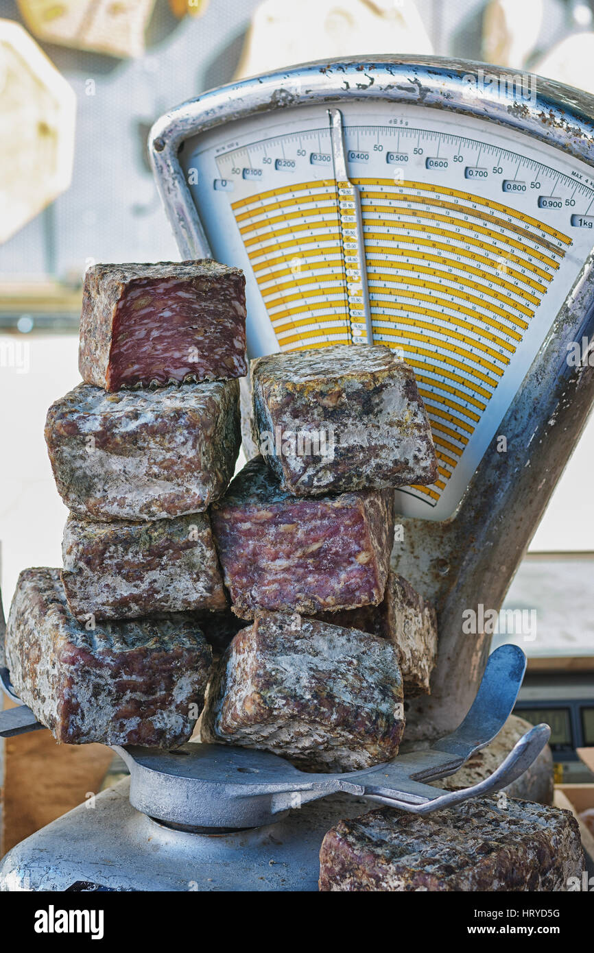 French sausages pyramid on the scales on the market. - Stock Image