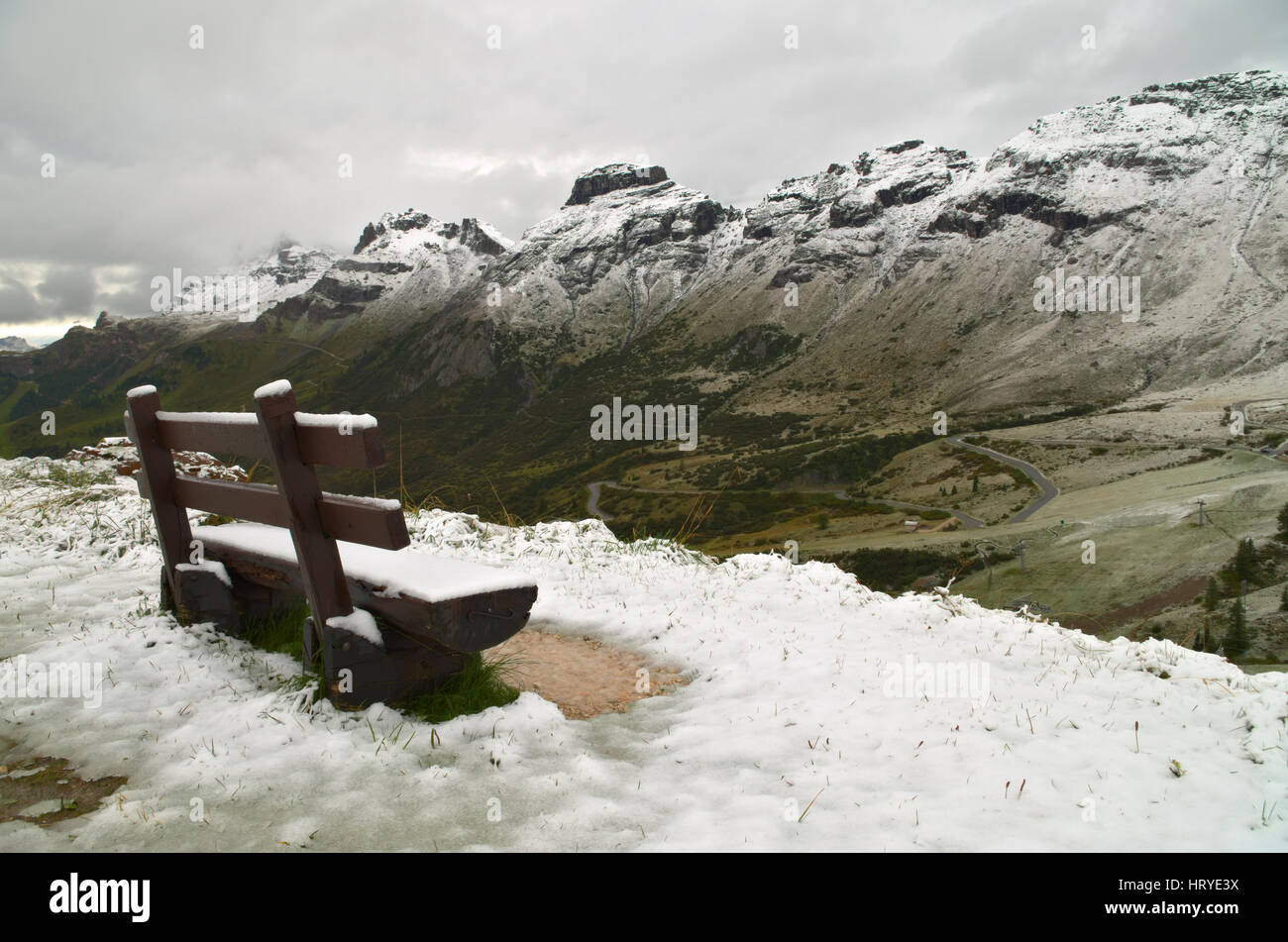 Passo Pordoi: bench covered by the first snow of the season on the Dolomiti mountains - Stock Image