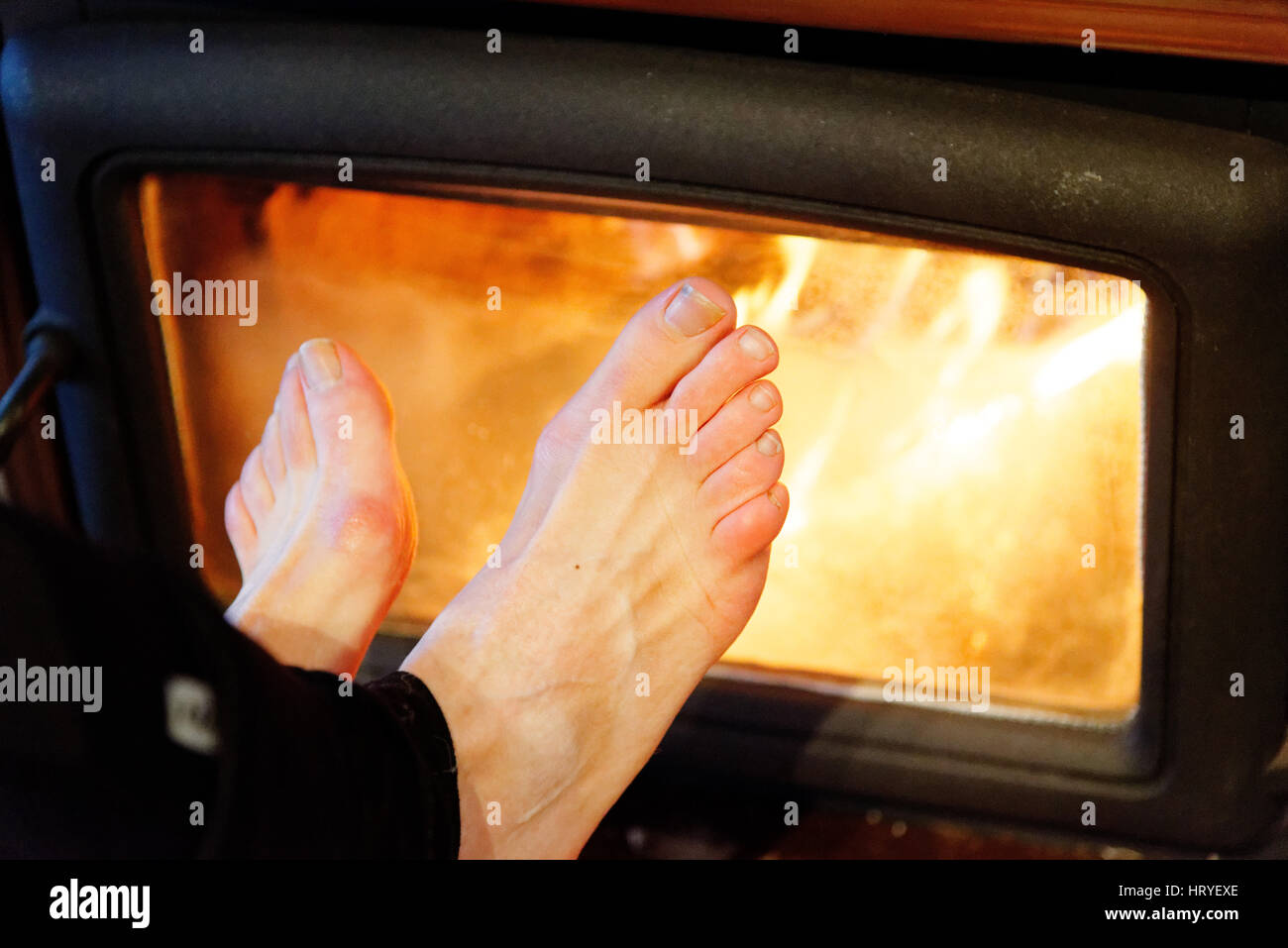 Cold feet warming in front of a blazing fire - Stock Image