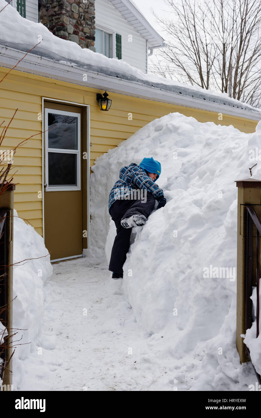 A young boy (4 yr old) climbing on a big snowdrift outside a house in Quebec - Stock Image