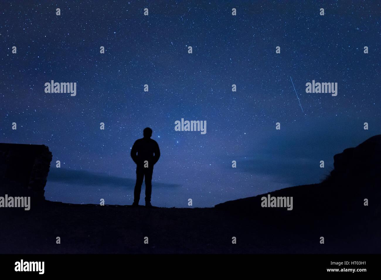 Man standing under stars at night - Cornwall, UK - Stock Image