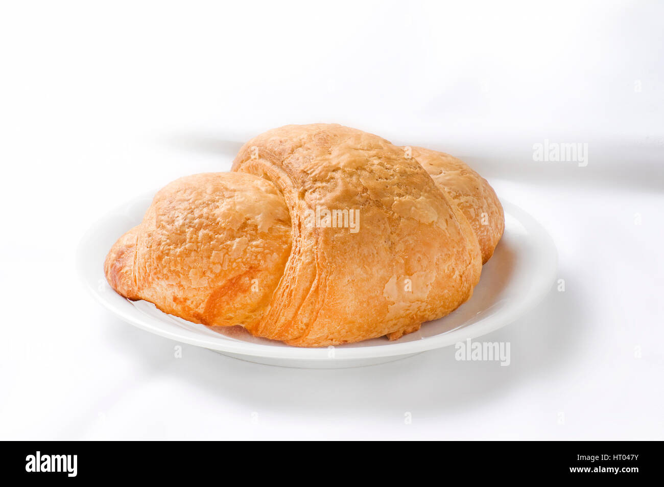 croissant on small plate o white background - Stock Image