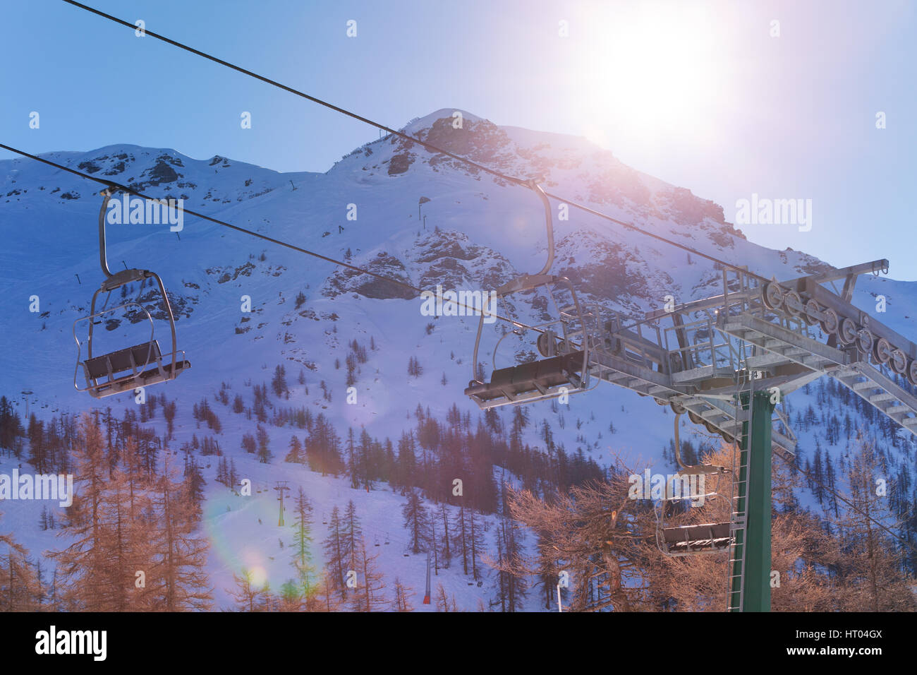 Beautiful mountain scene with empty chairlifts in the foreground at sunny day Stock Photo