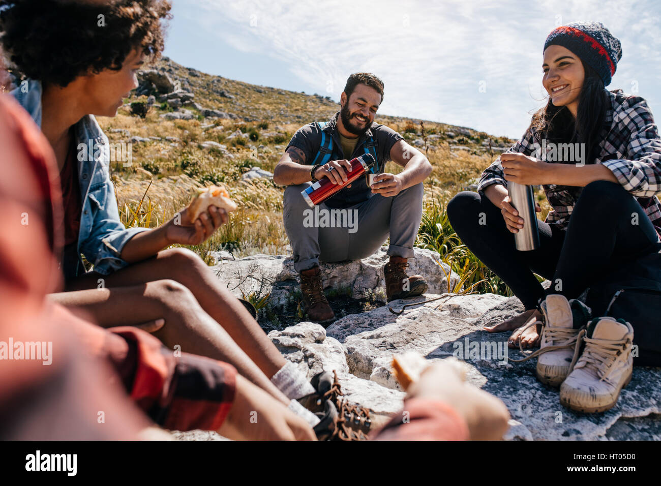 Group of hikers couple eating sandwiches and drinking coffee while relaxing in field. Young people having a rest during country hike. Stock Photo
