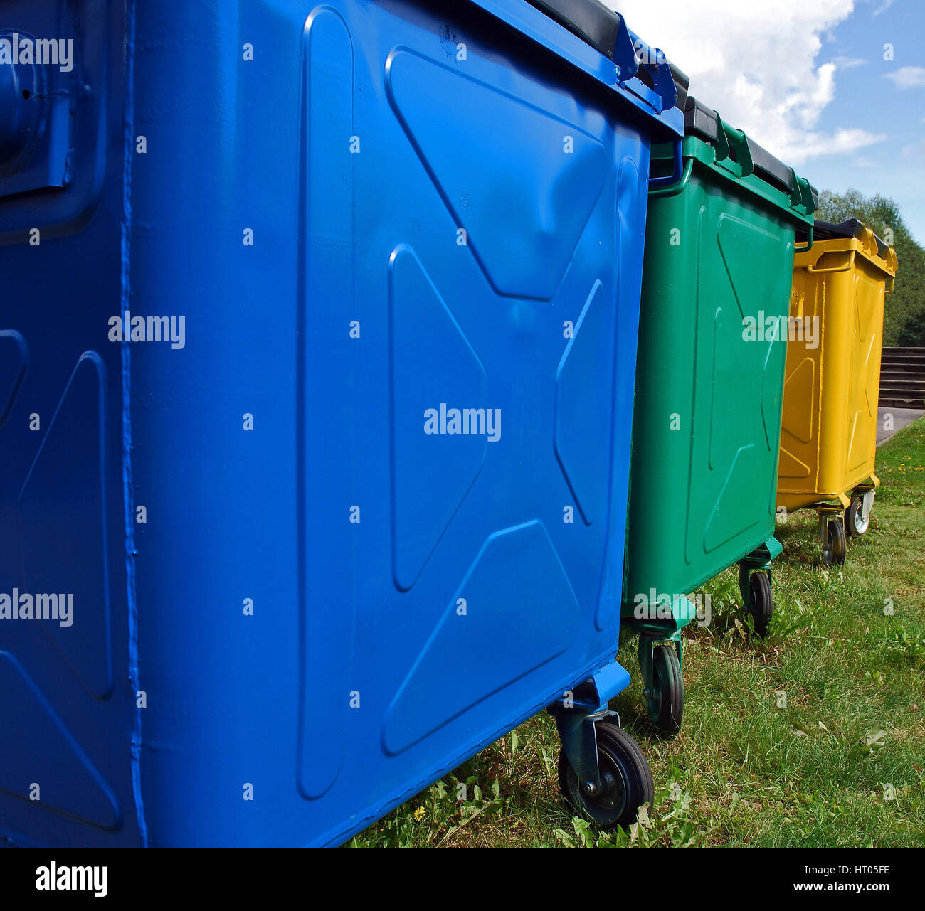 Three colour recycling trash bins for ecological waste sorting - Stock Image