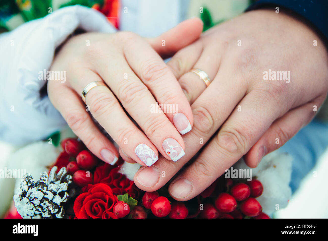 Bridal hands with rings on a bouquet of berries and cones with shallow depth of field - Stock Image