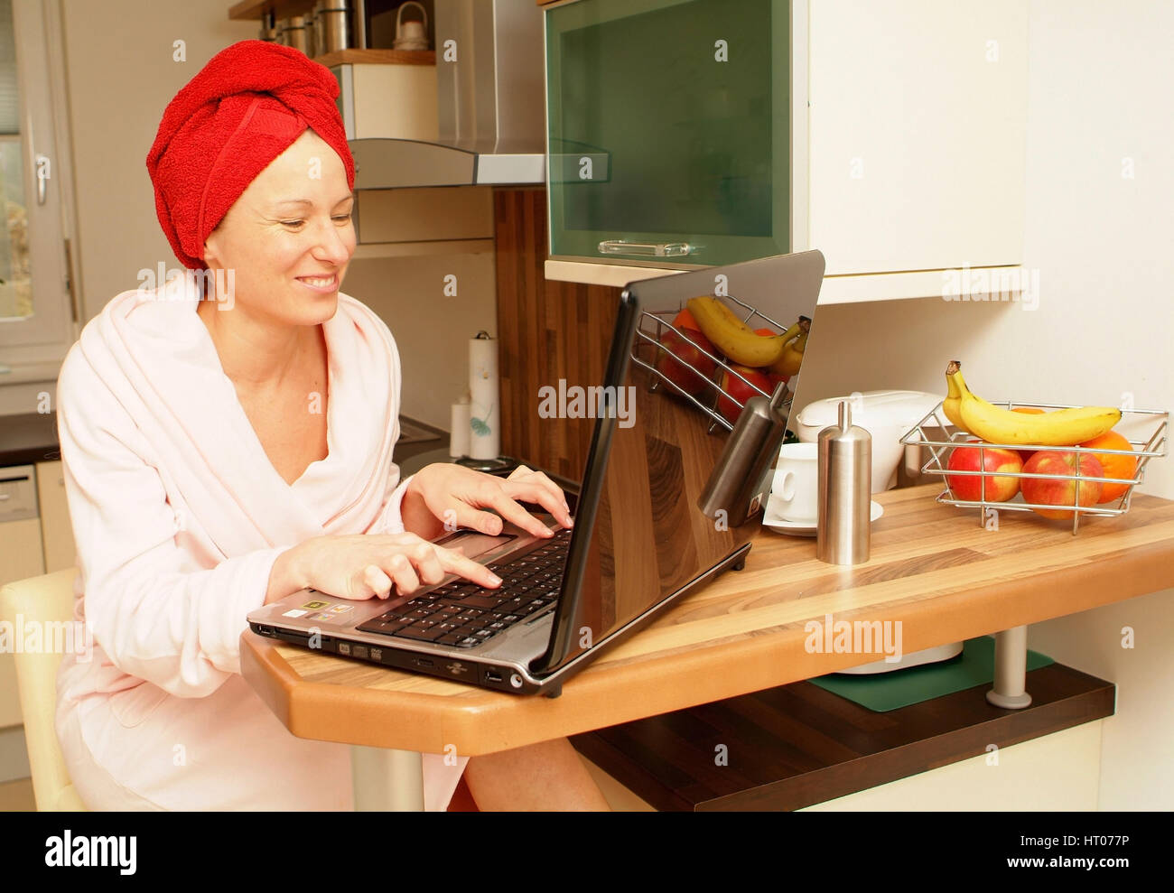Junge Frau im Morgenmantel arbeitet am Notebook in der Kueche - woman in bath robe using laptop in kitchen - Stock Image
