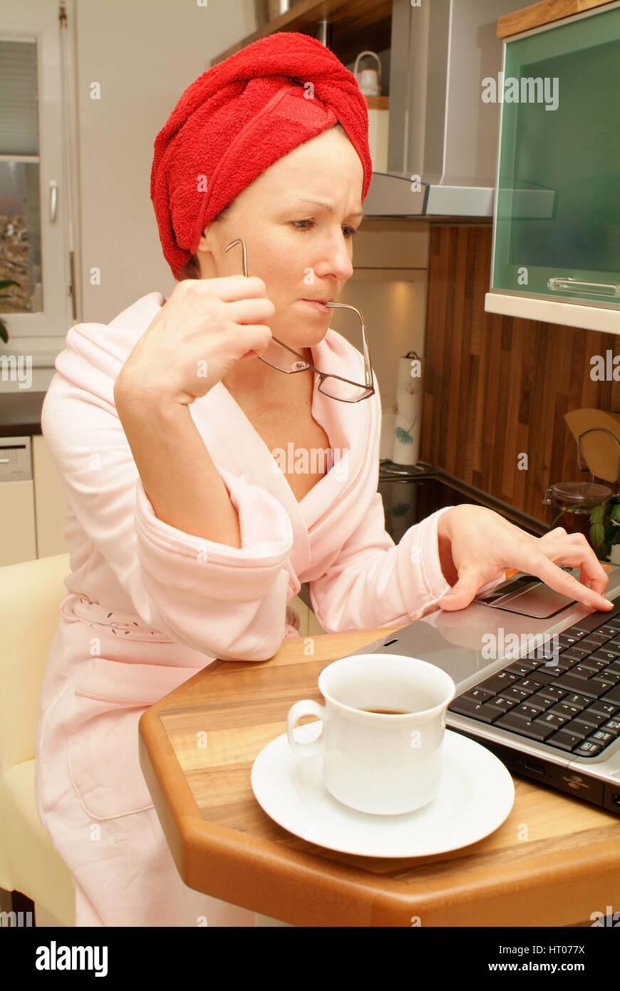 Junge Frau im Morgenmantel sitzt an der Kuechenbar und arbeitet am Notebook - young woman at home using laptop - Stock Image