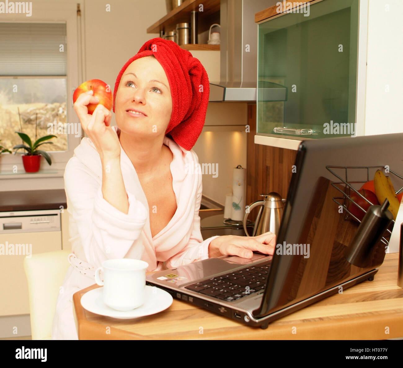Junge Frau im Morgenmantel arbeitet am Notebook und isst einen Apfel - young woman in bath robe using laptop and - Stock Image
