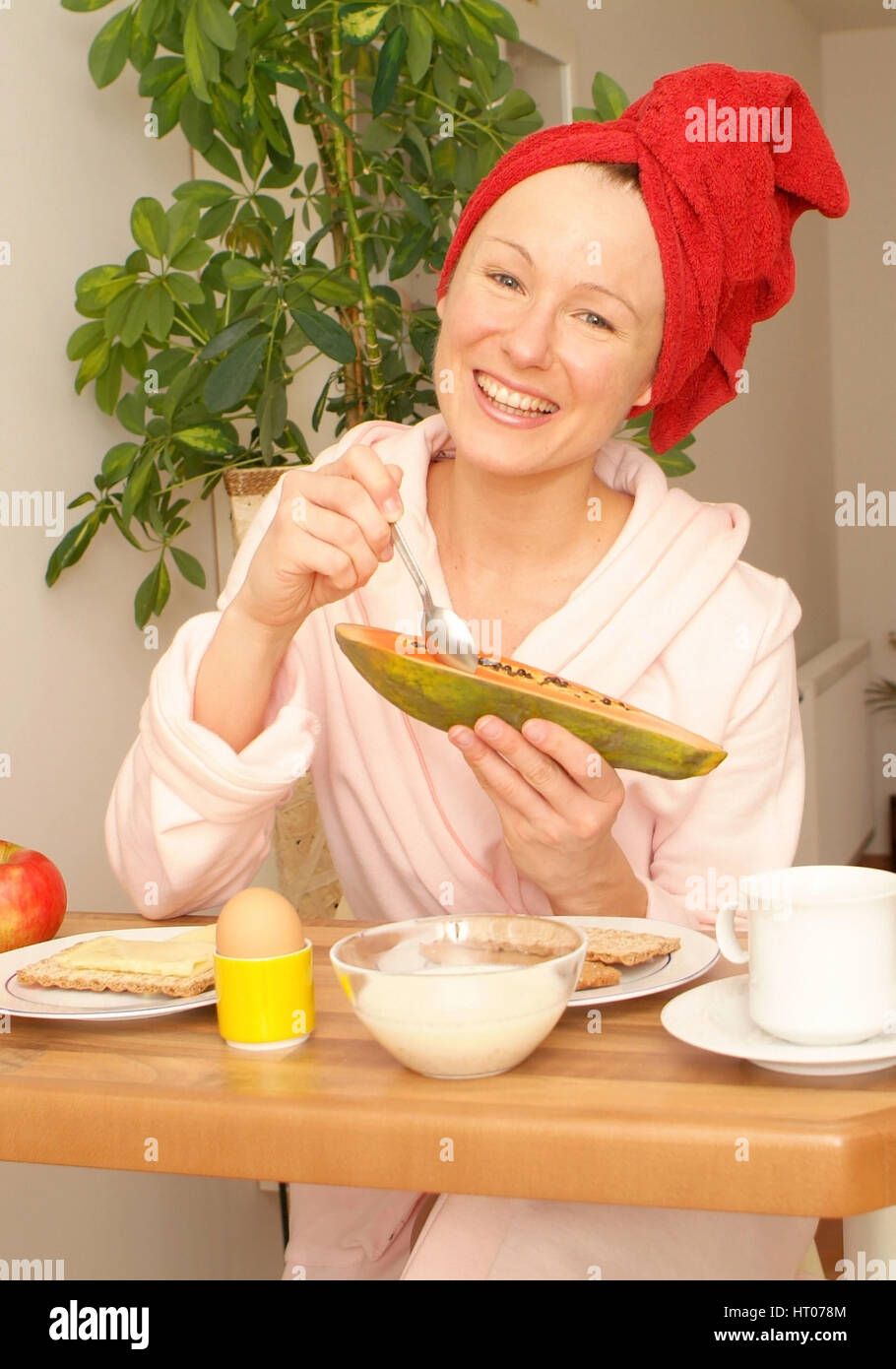 Junge Frau im Morgenmantel beim gesunden Fruehstueck - young woman in bathrobe at substantial breakfast - Stock Image