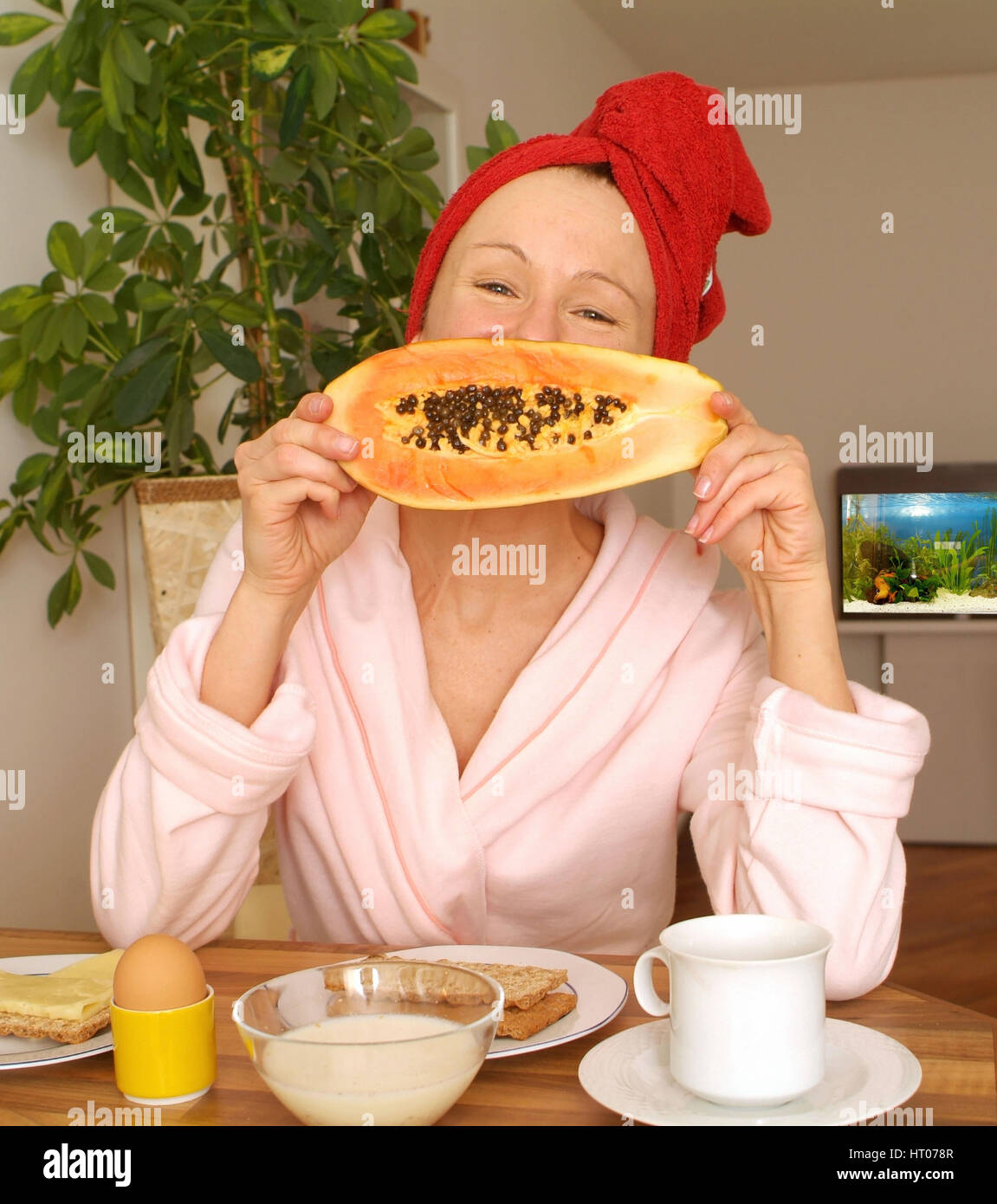 Junge Frau im Morgenmantel beim gesunden Fruehstueck - young woman at substantial breakfast - Stock Image
