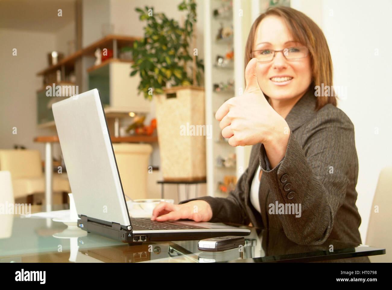 Erfolgreiche Geschaeftsfrau arbeitet von Zuhause am Notebook - Business woman homeworking on laptop Stock Photo