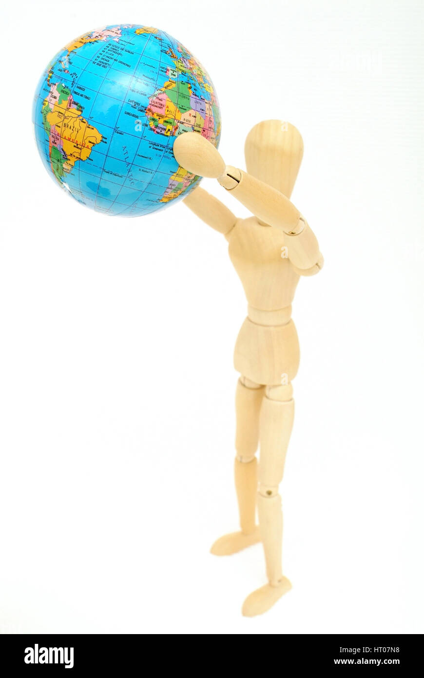 Holzfigur haelt Globus in der Hand - jointed doll with globe in hands - Stock Image