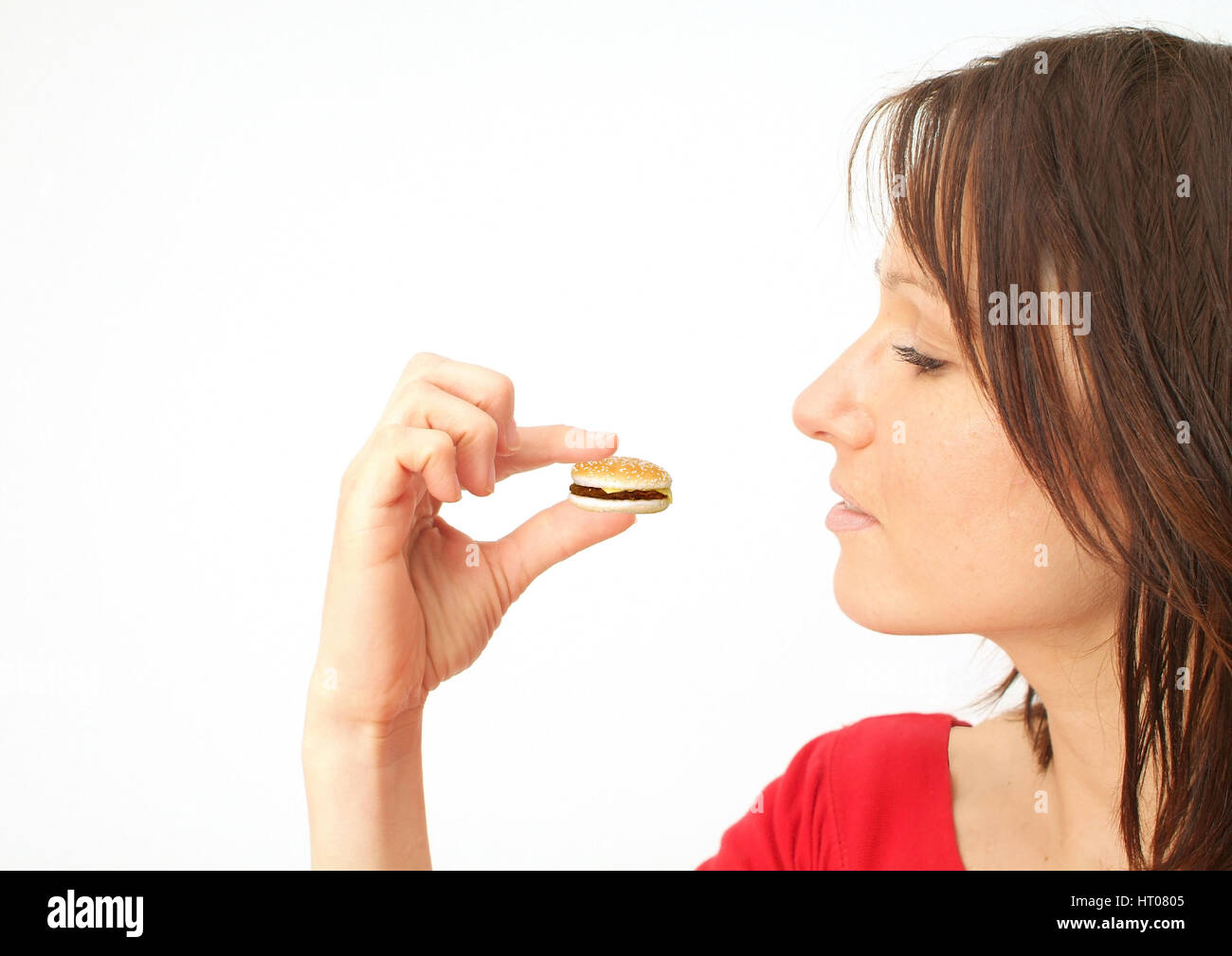 Symbolbild FdH, Frau mit Miniatur-Burger in der Hand - symbolic for Eat the Half, woman with miniature burger - Stock Image