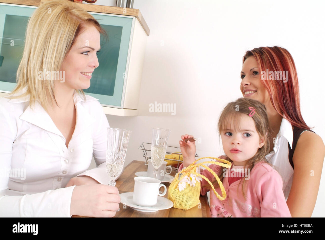 Zwei Freundinnen mit Kind beim gemuetlichen Beisammensitzen an der Kuechenbar - two friends with child get-together - Stock Image