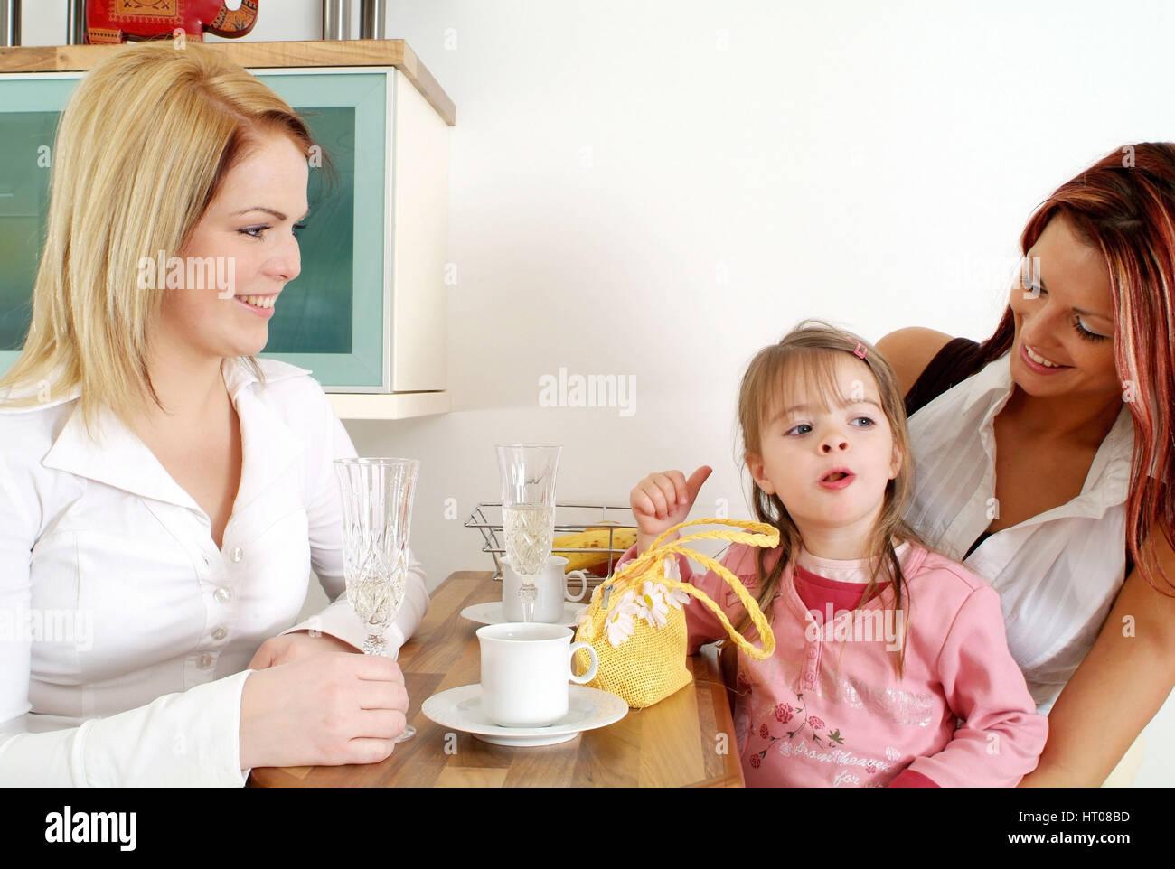 Zwei Freundinnen mit Kind beim gemuetlichen Beisammensitzen an der Kuechenbar - two friends with child get-together - Stock Image