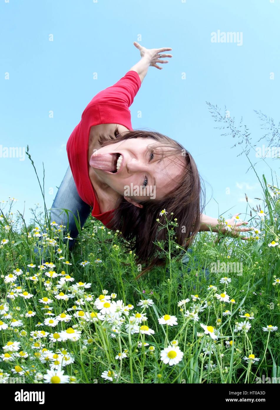 Ausgelassene, junge Frau steht in der Wiese und zeigt die Zunge - frolic young woman in meadow - Stock Image