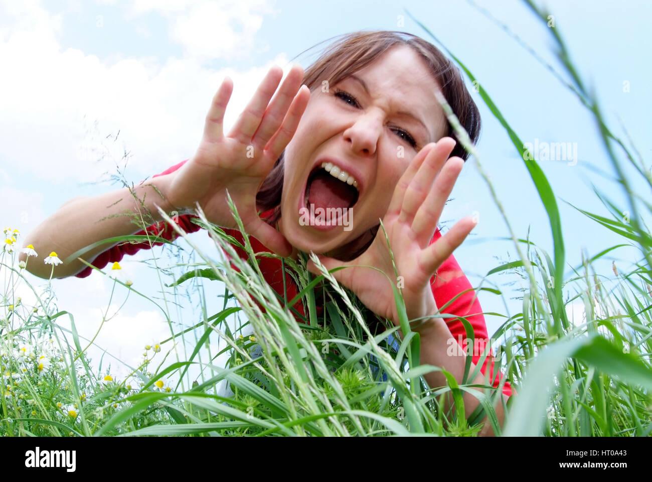 schreiende Frau im Gras - screaming woman in grass Stock Photo