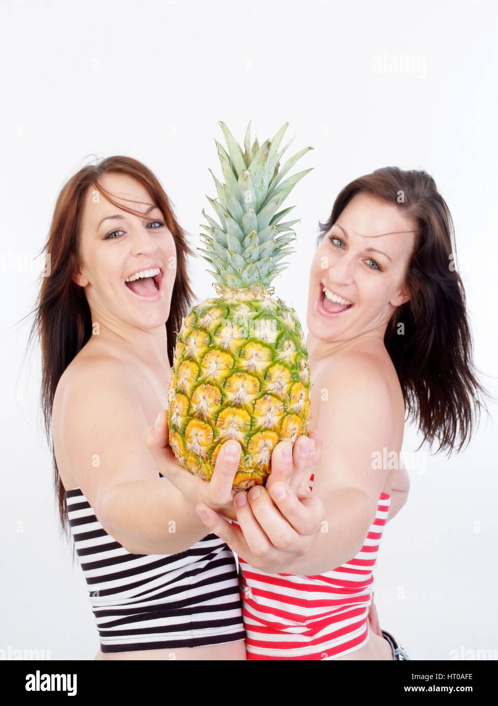 Fr?hliche Zwillinge mit Ananas - twins with pineapple - Stock Image