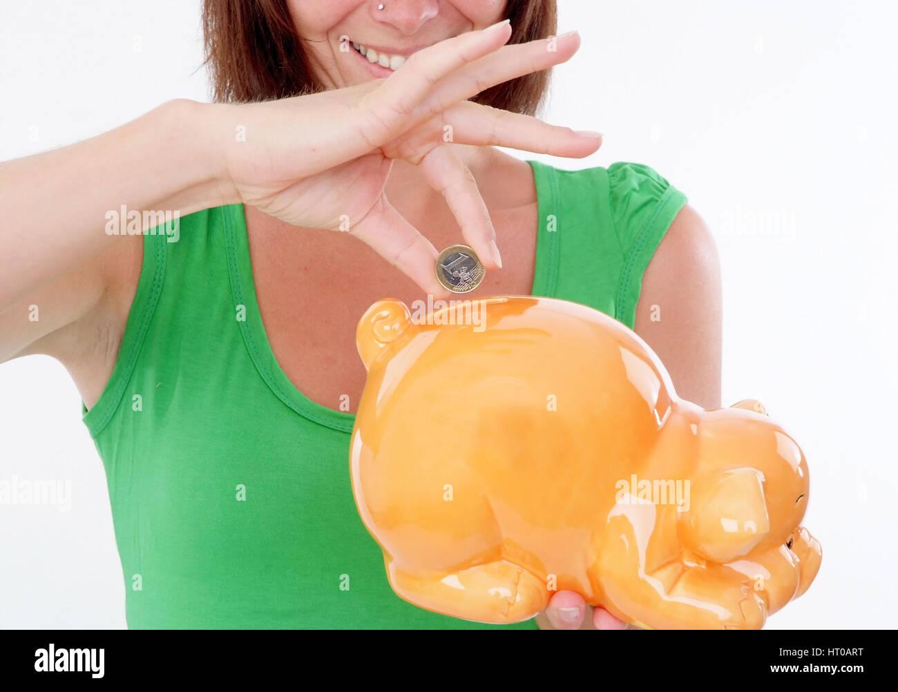 Frau wirft Euromuenze in Sparschwein - woman saving money Stock Photo