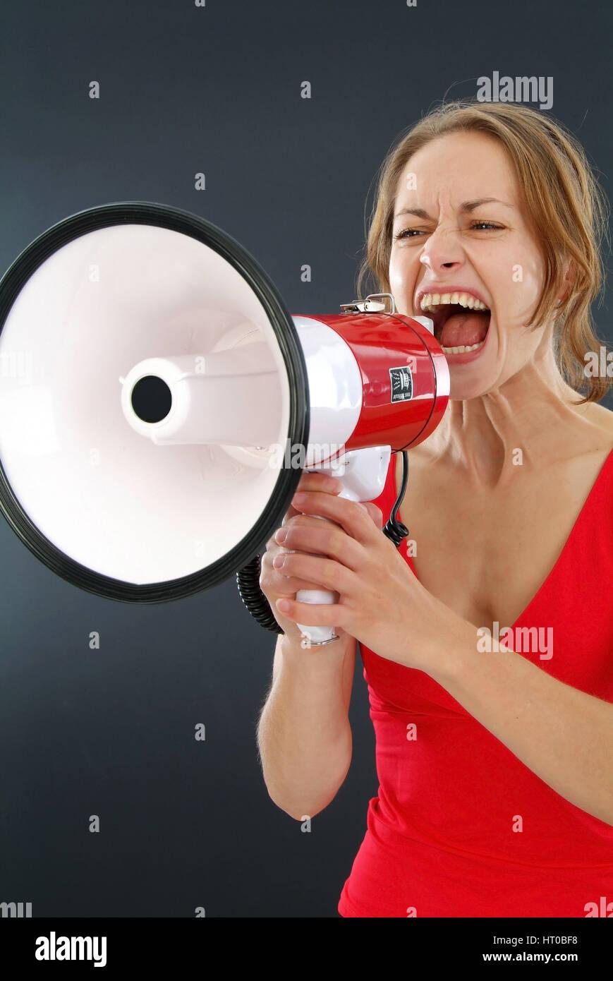 Junge Frau schreit in ein Megaphon - young woman screaming in a megaphone Stock Photo