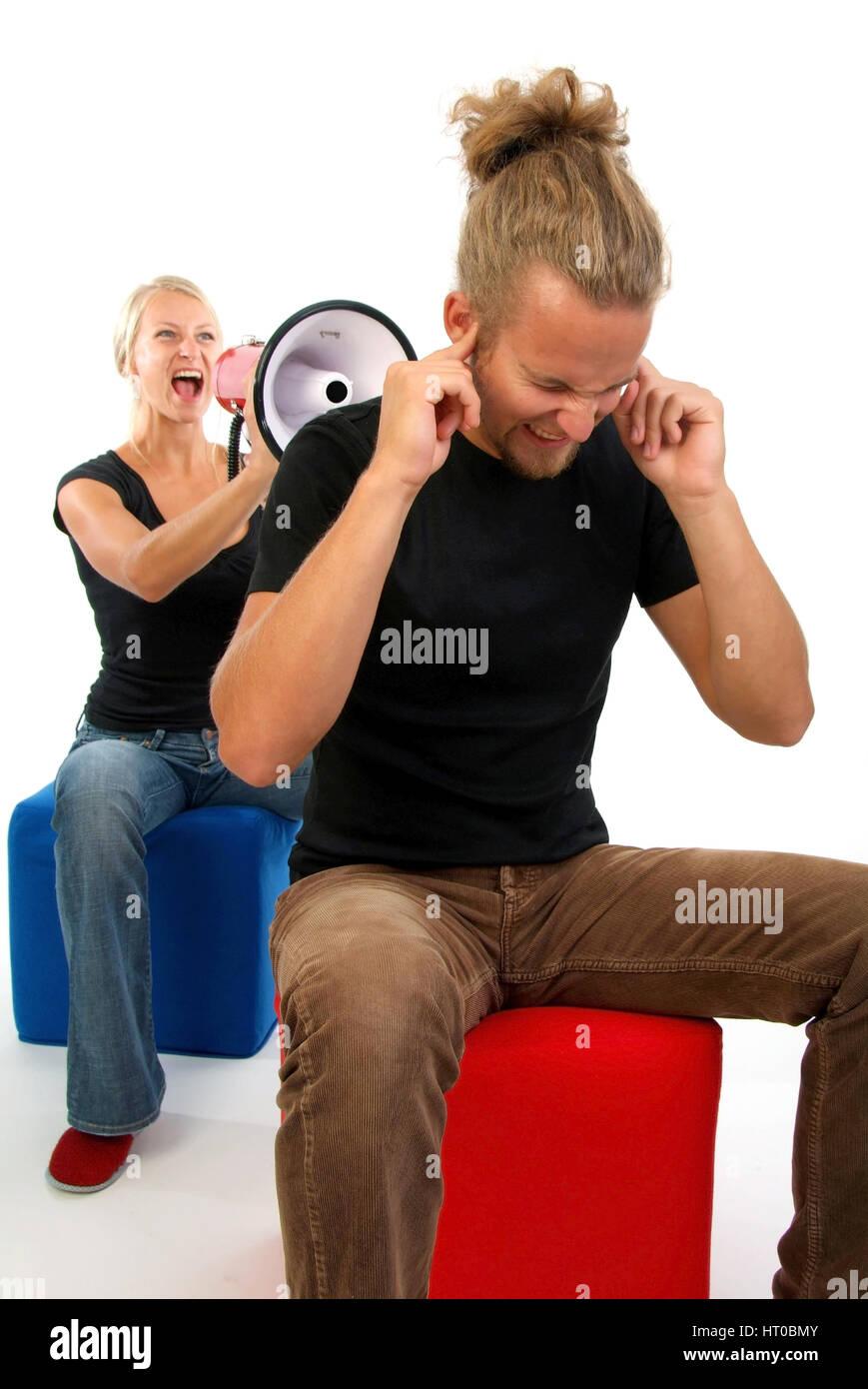 Symbolbild Beziehungskrise, Junge Frau schreit in Megaphon, Mann h?lt dsich die Ohren zu - symbolic for marital quarrel Stock Photo