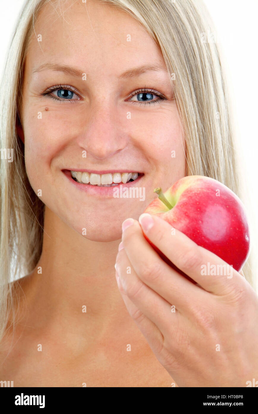 Junge, blonde Frau mit Apfel - young, blond woman with an apple - Stock Image