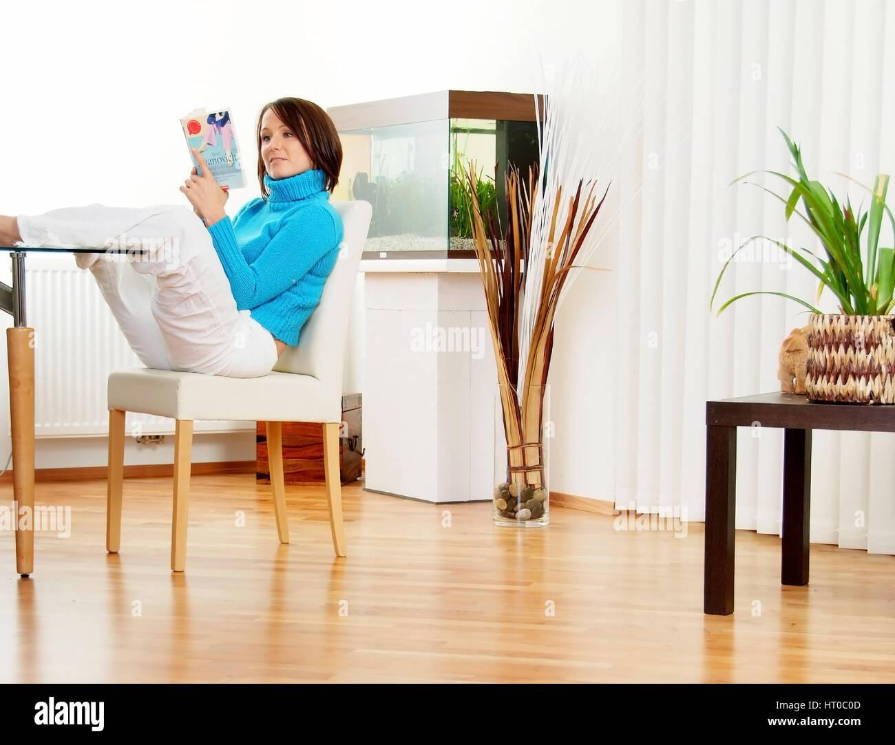 Junge Frau sitzt gem?tlich am Esstisch im Wohnzimmer und liest ein ...
