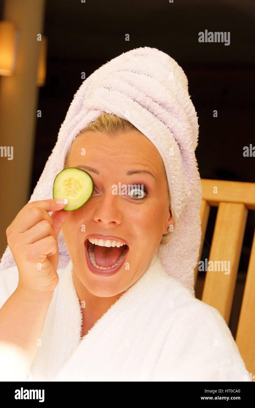 Junge, vitale Frau h?lt sich Gurkenscheibe vor das Gesicht - young, vital woman with cucumber - Stock Image