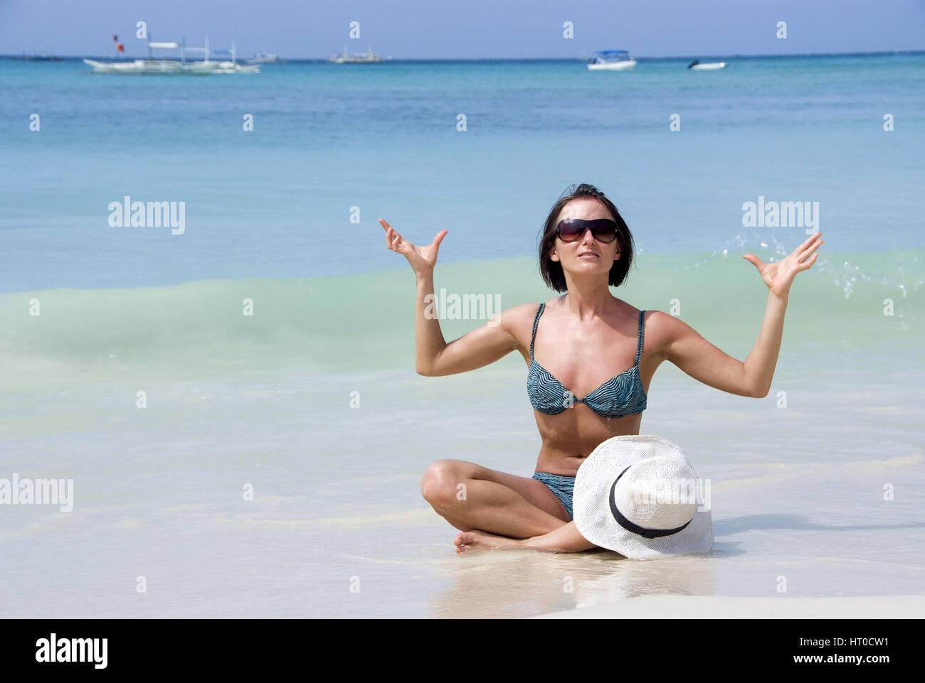 Frau macht Joga am Sandstrand - woman does yoga on the beach - Stock Image