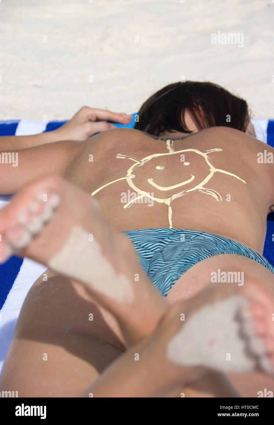 Frau beim Sonnen mit Sonnencreme in Form einer Sonne am R¸cken - woman suns with sun care Stock Photo