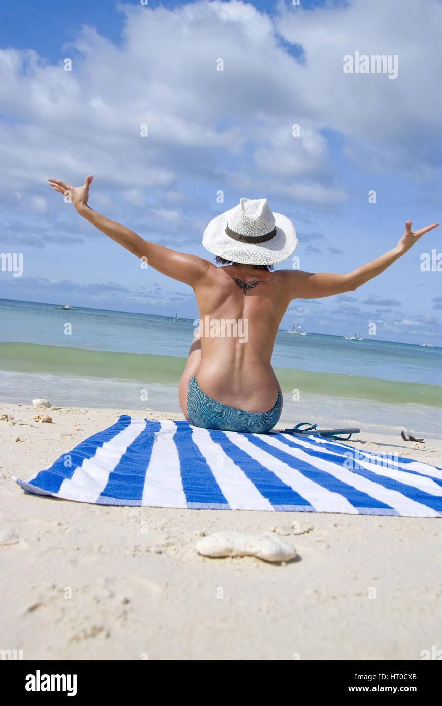 Junge Frau genie?t Strandurlaub - woman enjoying on the beach - Stock Image