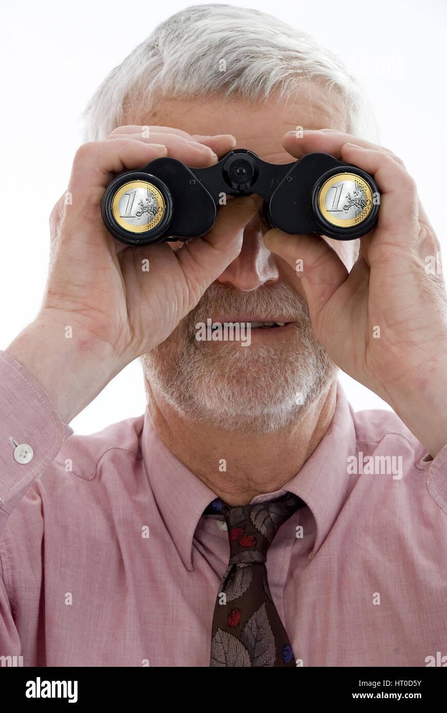 Pensionist schaut durch Fernglas mit Eurom¸nzen - retiree with spyglass - Stock Image