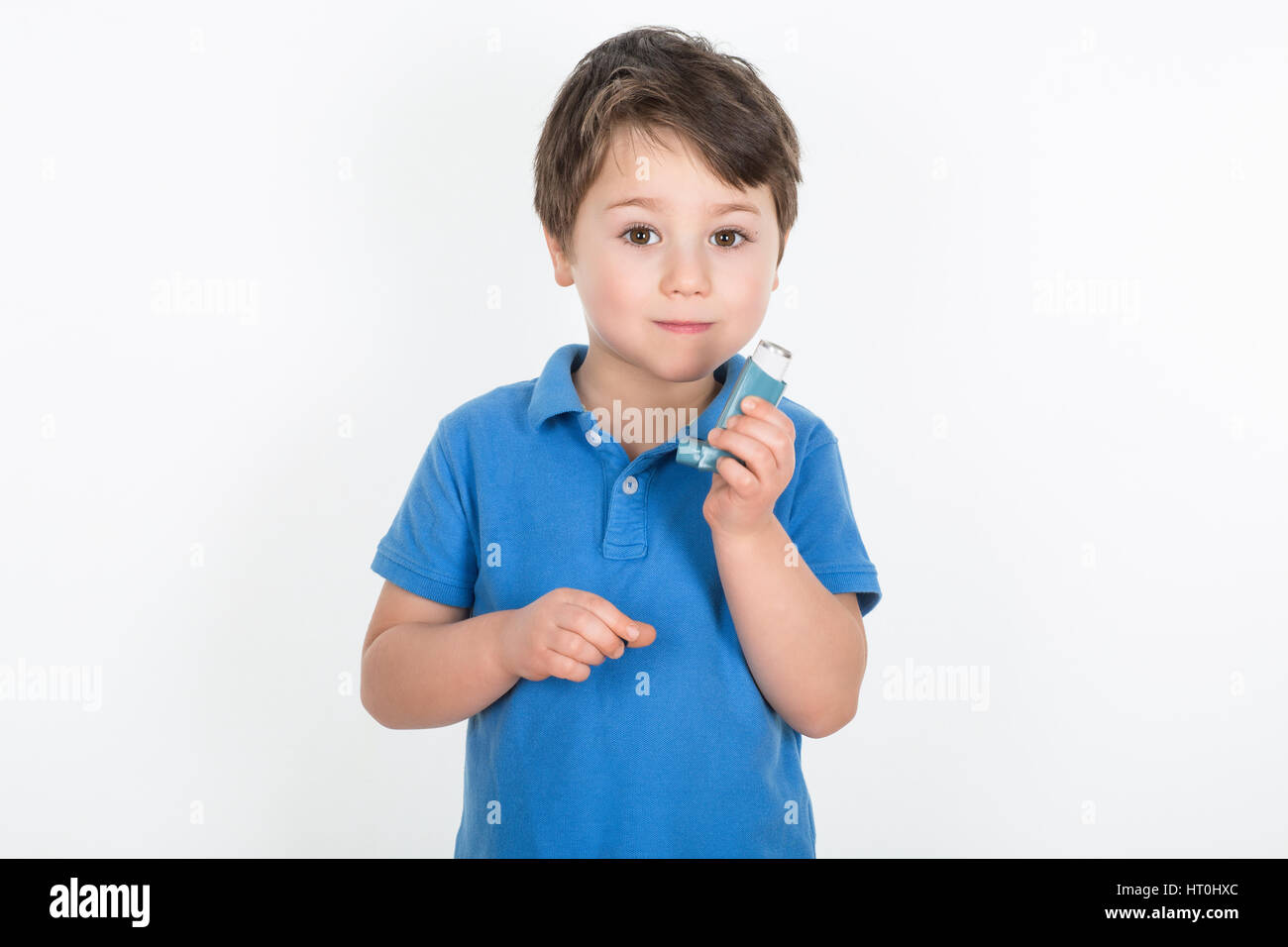 Little boy with asthma holding a metered-dose Inhaler 'Puffer'	. Isolated on a white background. - Stock Image
