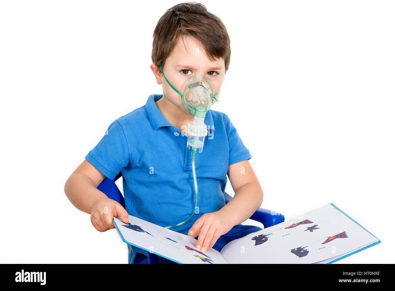 Asthmatic boy wearing face mask from nebulizer inhaler machine. Isolated on a white background. - Stock Image