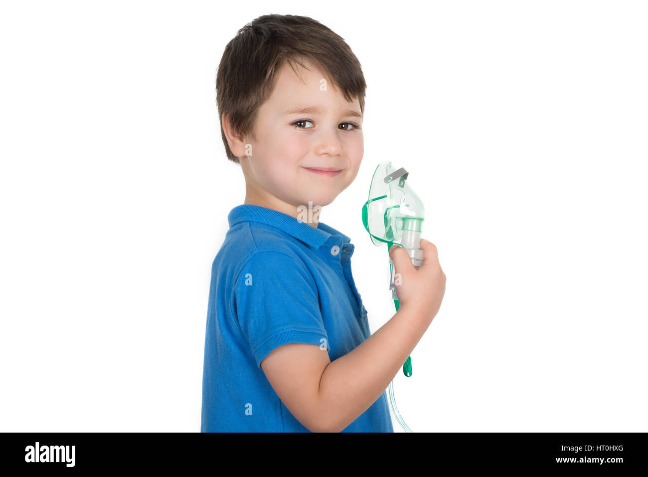 Little boy, asthma sufferer, holding in his hand face mask from nebulizer inhaler machine and smiling. Isolated - Stock Image