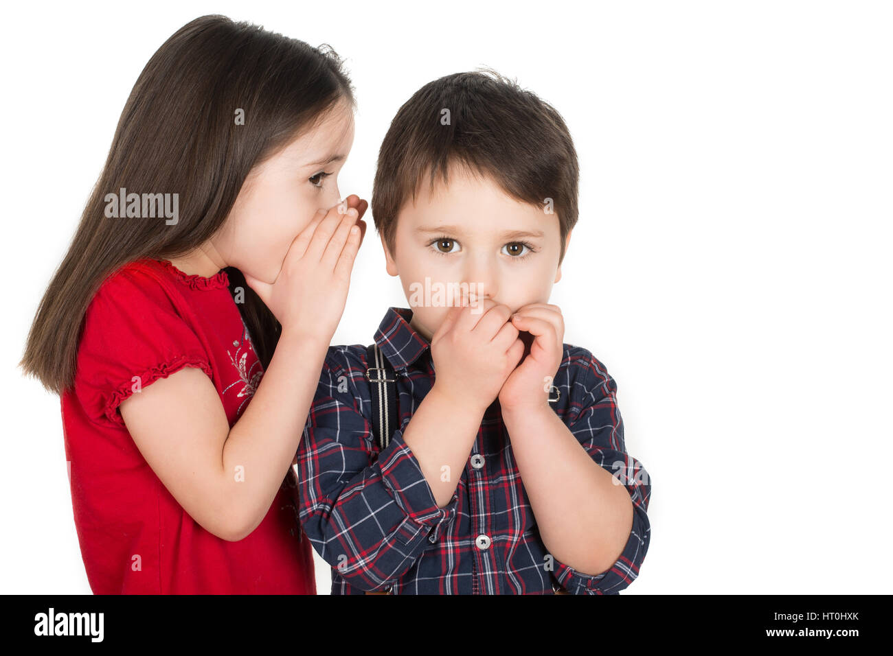 Girl whispering in a little boy`s ear. Boy covering his mouth with his hands. Scared or he cant believe. Isolated - Stock Image