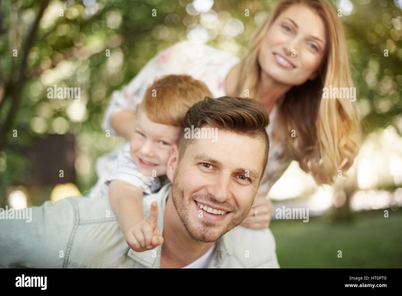 Portrait of happy family at the park - Stock Image