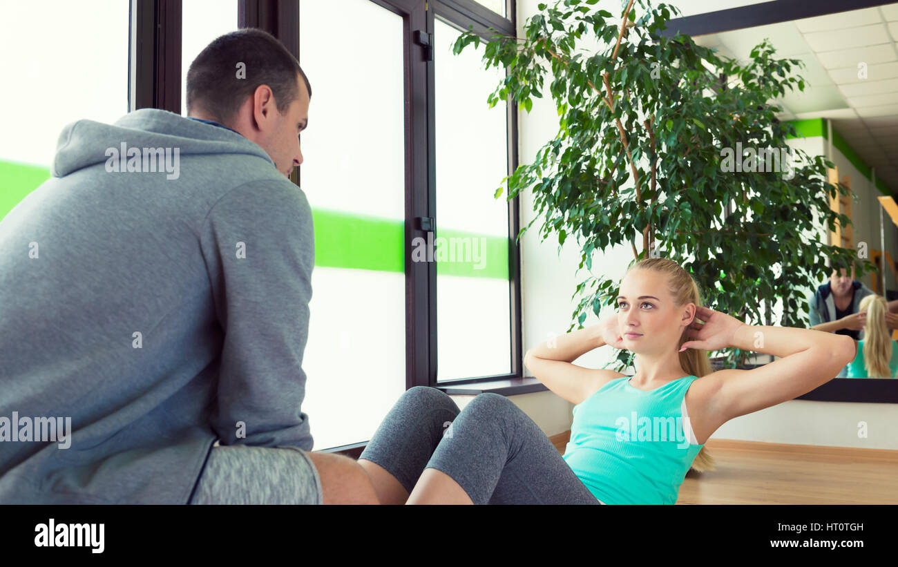 Personal trainer helping young attractive woman doing crunches in the gym - Stock Image