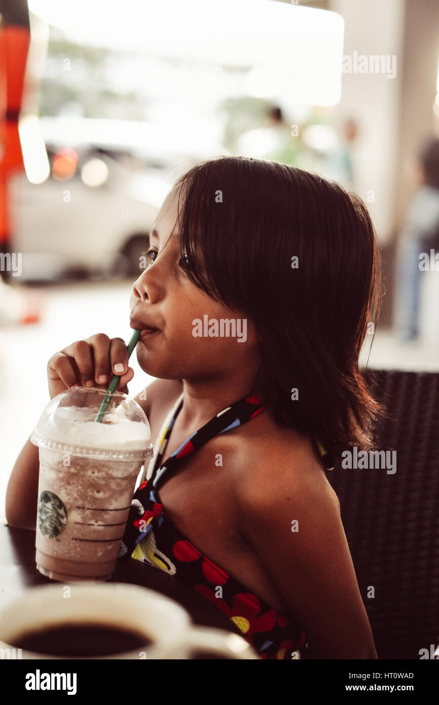 Cute Little Girl Drinking Ice Cold Chocolate Shake In A