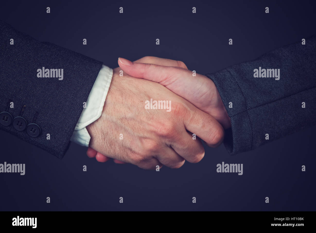 Joint venture, corporate people handshaking to form a temporary partnership by shared ownership over business undertaking - Stock Image