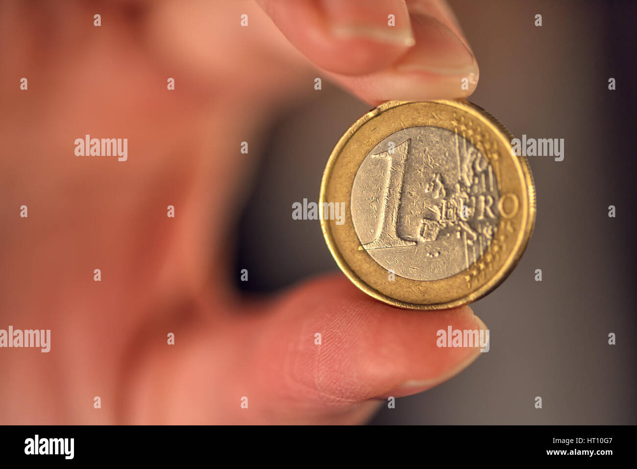 Macro of one euro coin between businesswoman fingers, european union currency - Stock Image